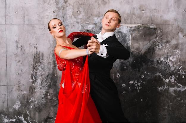 Para w tanecznej pozie blisko szarości ściany