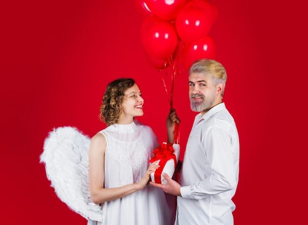 Para w walentynki. amorek anioł z prezentami i balonami. piękna para. walentynki.