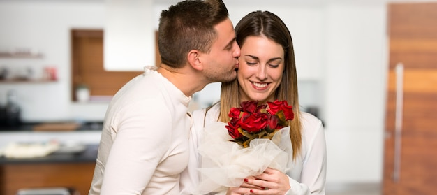 Para w walentynki z kwiatami w domu