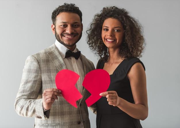 Para w wizytowym trzyma papierowe serce