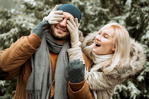 Para w zimie kobieta zakrywająca twarz swojego chłopaka
