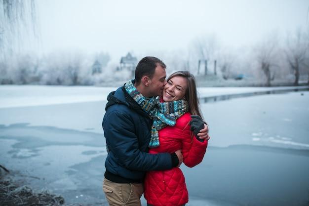 Para w zimowym lesie w pobliżu jeziora