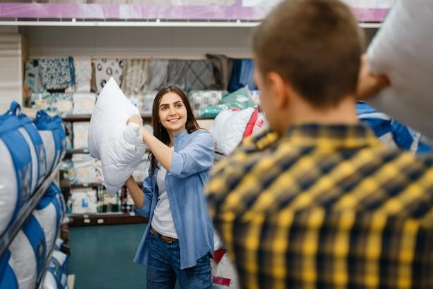 Para walcząca z poduszkami w sklepie z pościelą