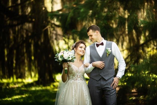 Para weselna lubi spacery po lesie. nowożeńcy obejmują i trzymają się za ręce