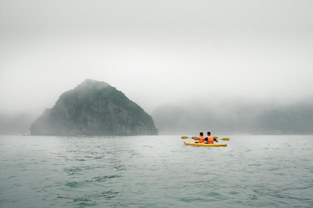 Para wiosłuje kajakiem w mglistą pogodę