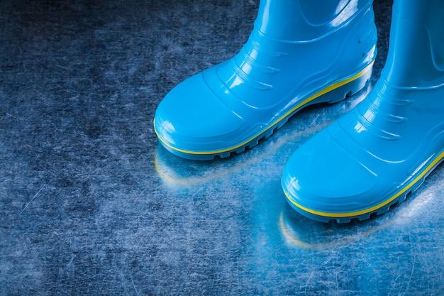 Para wodoodpornych butów gumowych na porysowanej metalicznej powierzchni