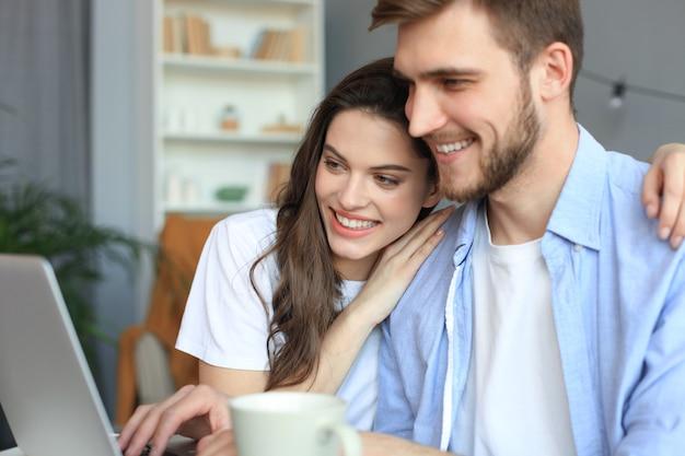Para wskazując podczas wspólnej pracy na laptopie.