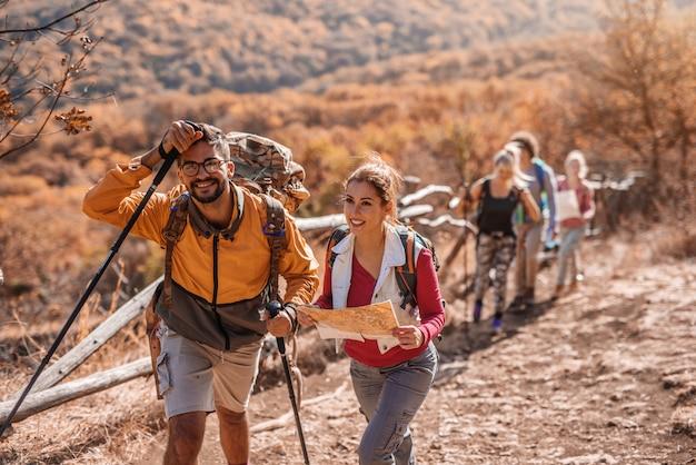 Para wspina się na wzgórze i rozmawia. kobieta trzyma mapę.
