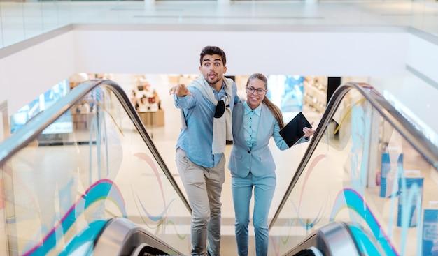 Para wspinająca się po ruchomych schodach i pędzi po coś do kupienia.