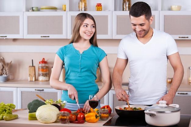 Para wspólne gotowanie. szczęśliwa młoda para gotuje razem w kuchni