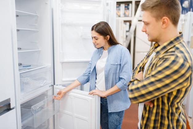 Para wybiera lodówkę w sklepie elektronicznym