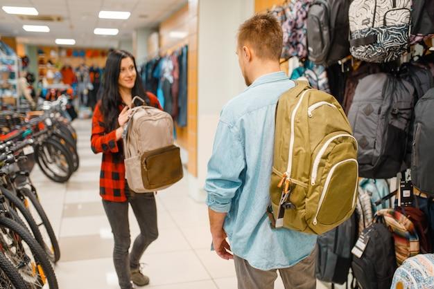 Para wybiera plecaki do podróży, zakupy w sklepie sportowym.