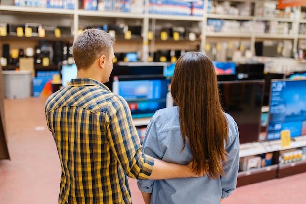 Para wybiera telewizor w sklepie elektronicznym