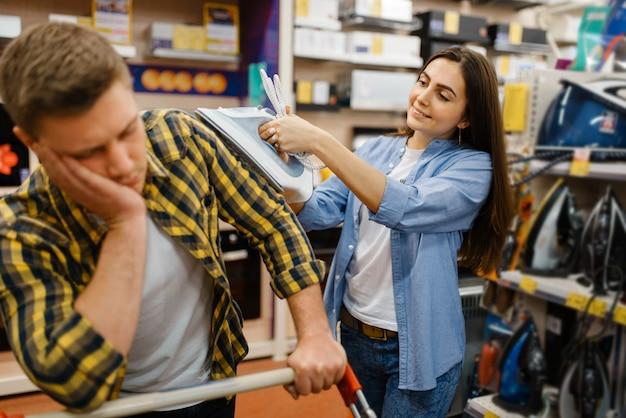 Para wybierając żelazko elektryczne w sklepie elektronicznym