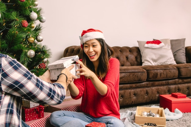 Para wymienia prezenta pudełko obok choinki