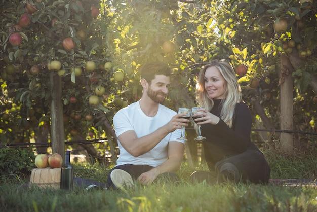 Para wznosi toast szkła wino w jabłczanym sadzie
