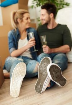 Para wznosząca toast na podłodze nowego mieszkania