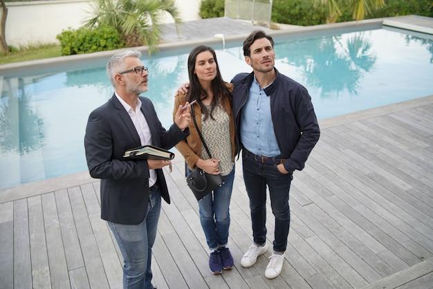 Para z agentem nieruchomości odwiedzającym nowoczesny dom