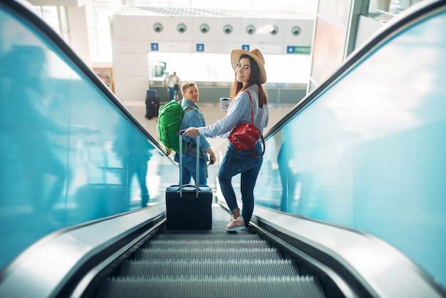 Para z bagażem wspina się po schodach ruchomych