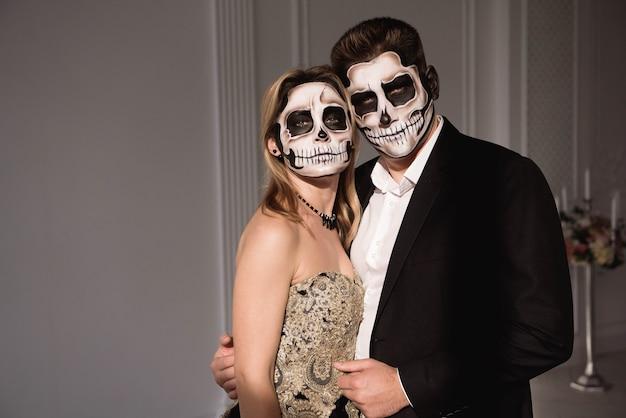 Para z ciemnym makijażem czaszki na białej przestrzeni