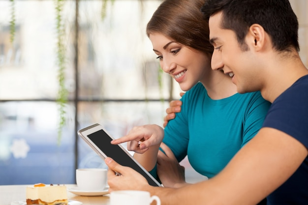 Para z cyfrową tabletką. widok z boku wesołej młodej pary kochającej się siedzącej w restauracji i korzystającej z cyfrowego tabletu