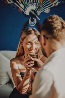 Para z dwojga podróżników spędza razem wakacje w tajlandii. radosna kobieta uśmiecha się i patrzy na swojego chłopaka w hotelu.