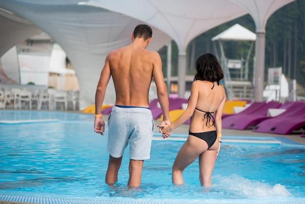 Para z idealną figurą w basenie