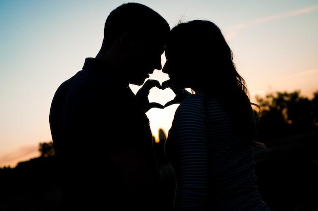 Para z kobieta w ciąży, trzymając się za ręce i zrobić kształt serca na brzuchu na zachód słońca