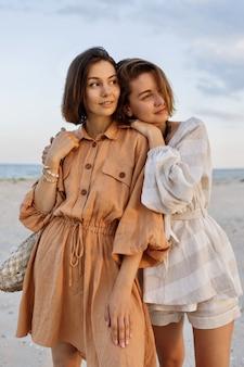 Para z krótką fryzurą w letnie ubrania lniane, pozowanie na plaży