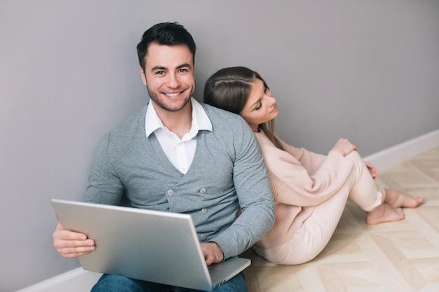 Para z laptopem siedząc na podłodze. zakupy online.