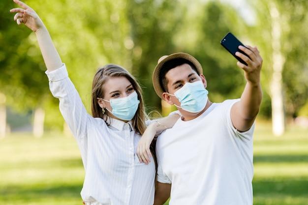 Para z maską przy selfie z telefonem komórkowym w parku