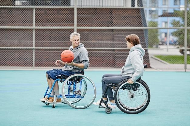 Para z paraplegią grająca w koszykówkę na świeżym powietrzu