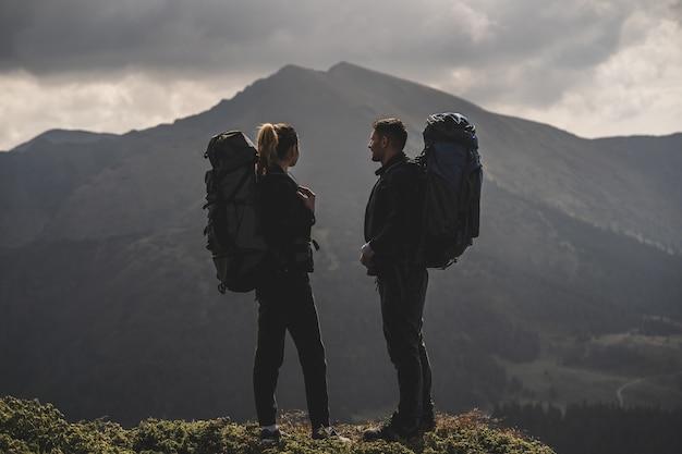 Para z plecakami stojąca na tle górskiego krajobrazu