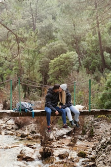 Para z plecakiem siedzi na moście