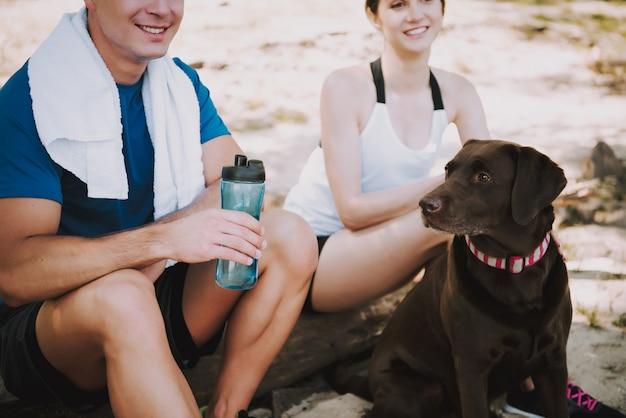 Para z psem na brzegu rzeki w wielkim parku