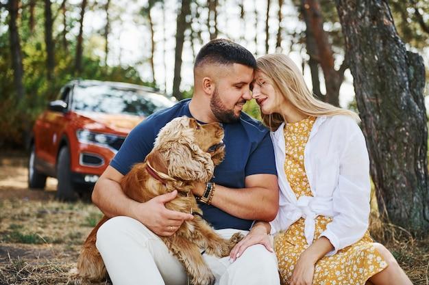 Para z psem spędza weekend na świeżym powietrzu w lesie z samochodem za nimi.