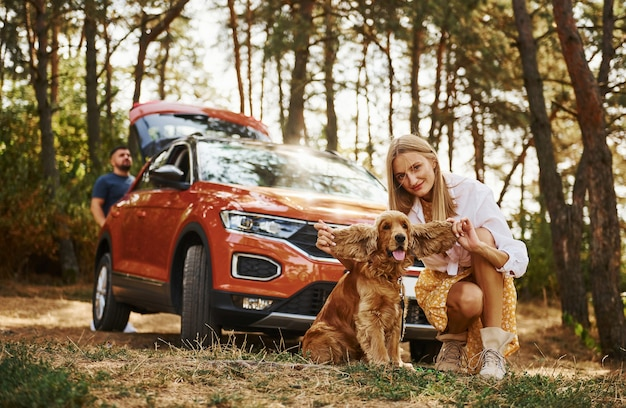 Para z psem spędza weekend na świeżym powietrzu w lesie z samochodem.
