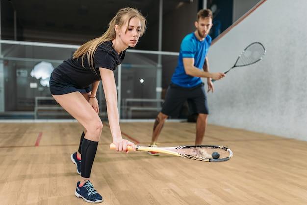 Para z rakietami do squasha, kryty klub treningowy