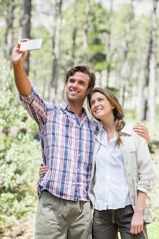 Para z rękami dookoła klikając selfie z inteligentnego telefonu