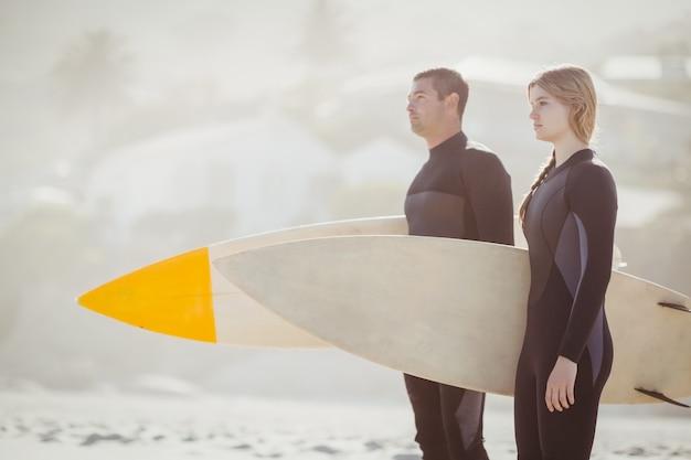 Para z surfboard pozycją na plaży