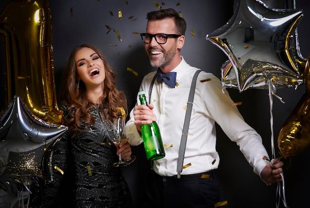 Para z szampanem i okularami, śmiejąc się