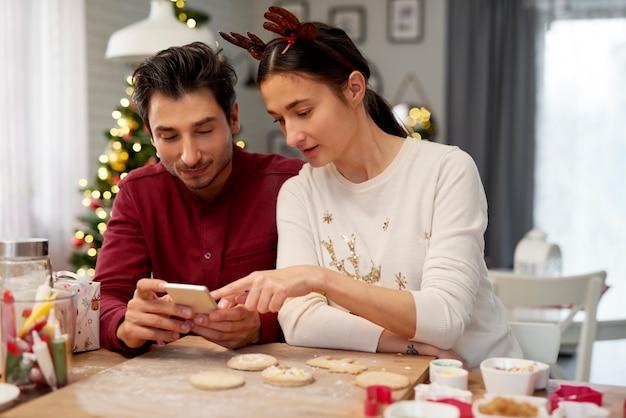 Para z telefonem komórkowym w kuchni