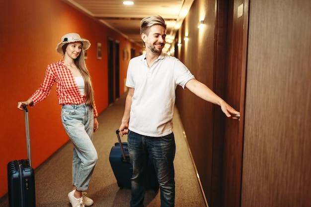 Para z walizkami szuka swojego pokoju hotelowego