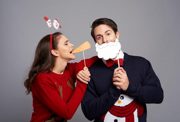 Para z zabawnymi maskami bożonarodzeniowymi