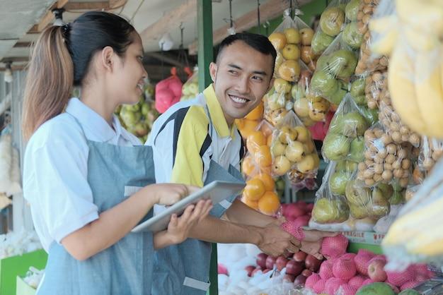Para za pomocą cyfrowego tabletu przy wyborze jabłka podczas przygotowywania ekspozycji sklepu z owocami