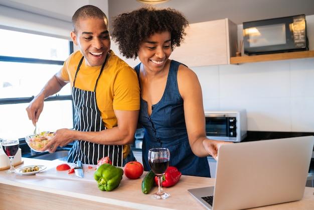 Para za pomocą laptopa podczas gotowania w kuchni