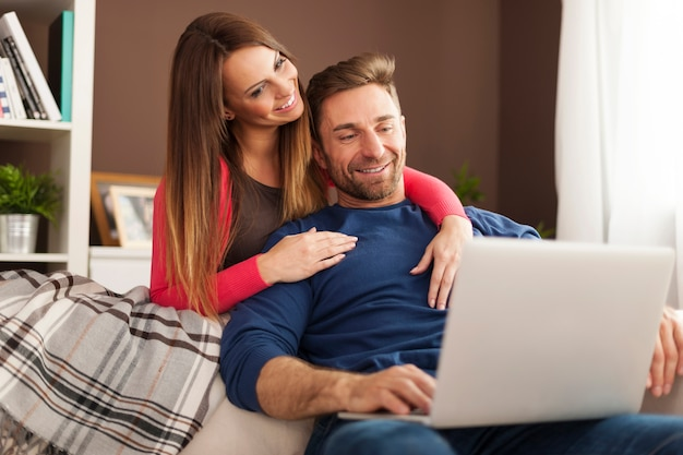 Para za pomocą laptopa razem siedząc na kanapie w domu