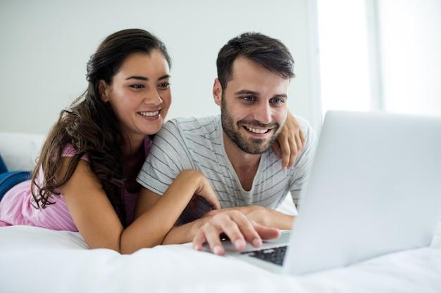 Para za pomocą laptopa w sypialni w domu