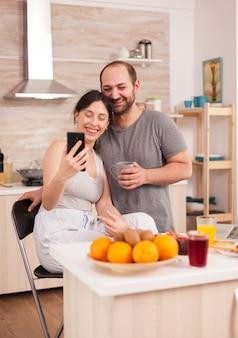 Para za pomocą smartfona do selfie, bawi się w kuchni. radosny żonaty mąż i żona robiąc śmieszne miny podczas robienia zdjęć podczas śniadania w kuchni.