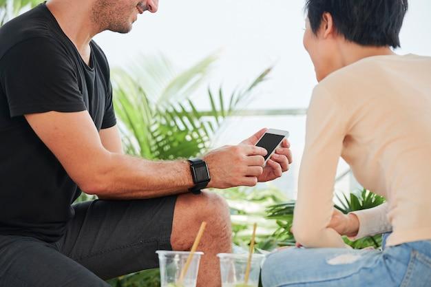 Para za pomocą smartfona w kawiarni